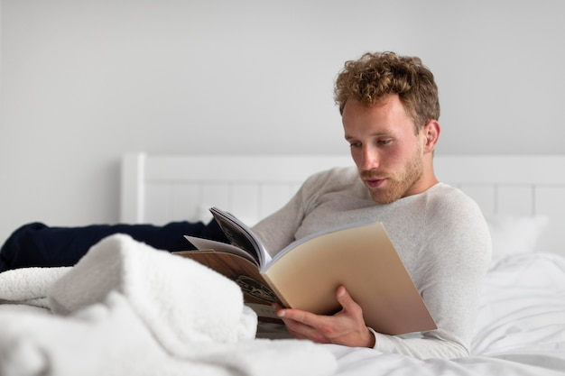 Homme plein coup lisant un livre dans la chambre