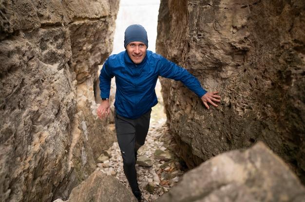 Homme plein coup marchant à travers les rochers