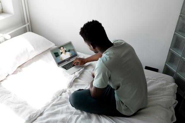 Homme plein coup avec ordinateur portable au lit