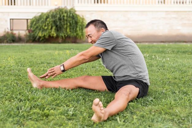 Homme plein coup qui s'étend sur l'herbe