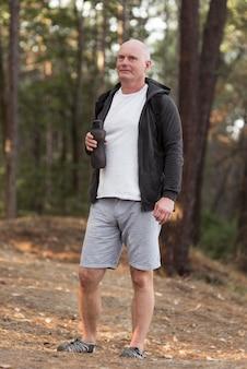 Homme plein coup tenant une bouteille d'eau