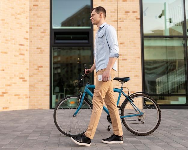 Homme plein coup tenant un vélo