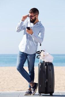 Homme de pleine longueur debout sur la plage avec valise et téléphone portable