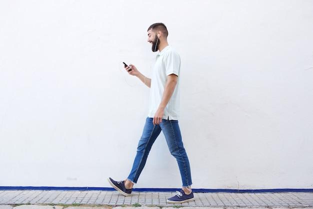 Homme de pleine longueur marchant et tenant un téléphone portable avec des écouteurs