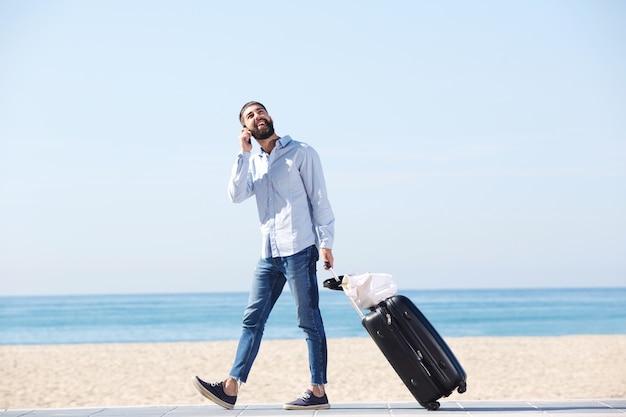 Homme pleine longueur, parler au téléphone portable avec des bagages sur la plage