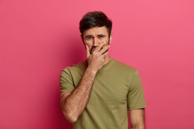 L'homme pleure de désespoir, a une expression triste, se couvre la bouche avec la main