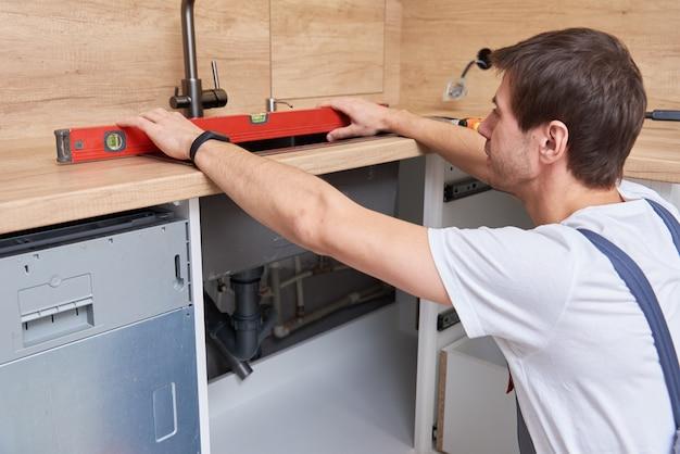 Homme plombier installe un évier dans la cuisine