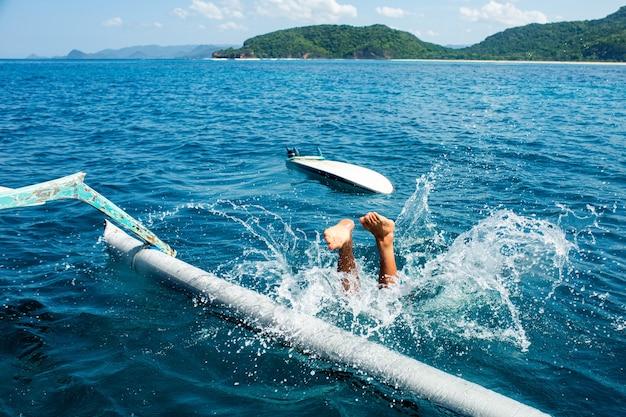 L'homme plonge dans l'eau.