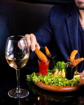 Homme plongeant les crevettes frites dans une sauce chili douce dans un verre à liqueur