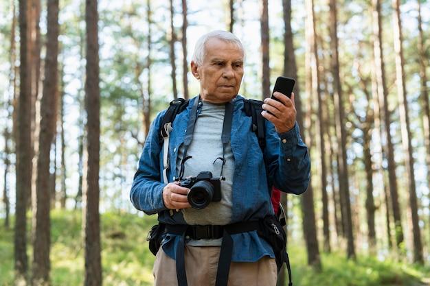 Homme plus âgé avec appareil photo et smartphone explorant la nature