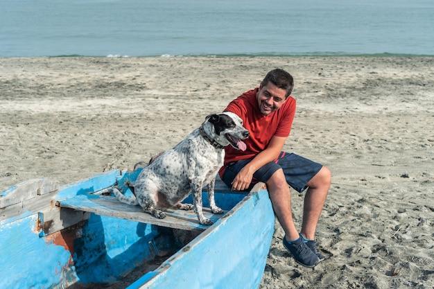 Homme plus âgé avec un chien noir et blanc à la plage