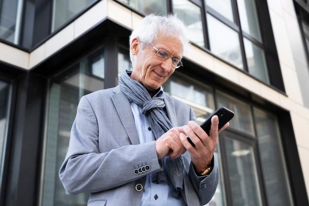 Homme plus âgé dans la ville à l'aide de smartphone