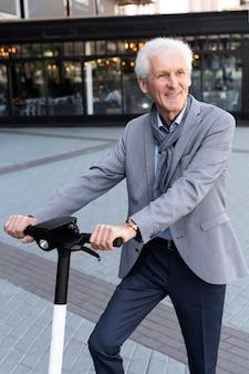 Homme plus âgé dans la ville avec scooter électrique