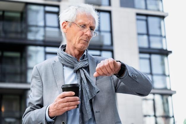 Homme plus âgé élégant dans la ville regardant smartwatch