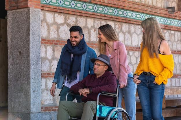 Homme plus âgé avec des lunettes et chapeau paralytique dans un fauteuil roulant accompagné d'un jeune latino-américain et de deux filles de race blanche se promenant joyeusement dans la rue