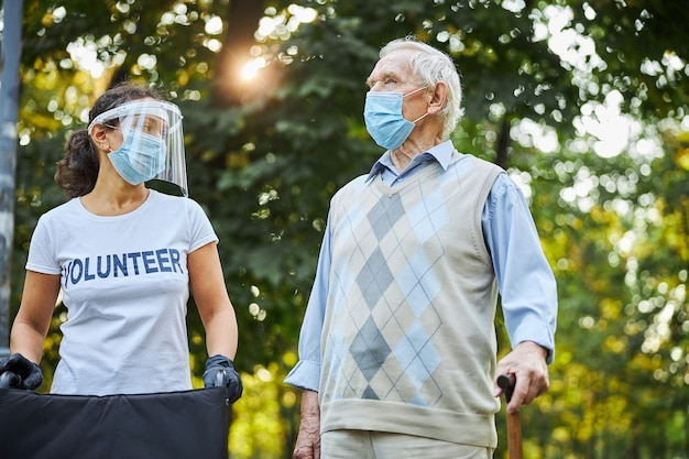 Homme plus âgé profitant du beau temps chaud sur la place de la ville avec un travailleur social