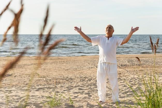 Homme plus âgé profitant de son temps à l'extérieur à la plage