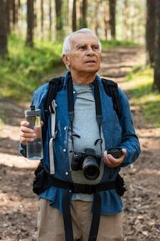Homme plus âgé, randonnée dans la nature avec appareil photo et bouteille d'eau