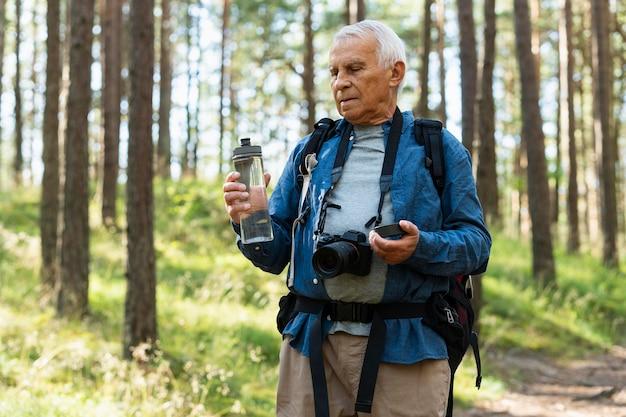 Un homme plus âgé reste hydraté tout en explorant la nature