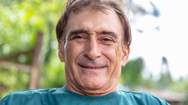 Homme plus âgé souriant sur la nature.