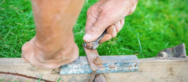 L'homme plus âgé tord l'écrou par la clé