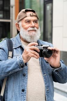 Homme plus âgé utilisant un appareil photo à l'extérieur de la ville pour prendre des photos