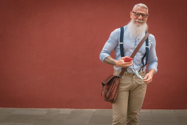 Un homme plus âgé en vêtements et lunettes hipster et une longue barbe blanche se promène en parlant au téléphone