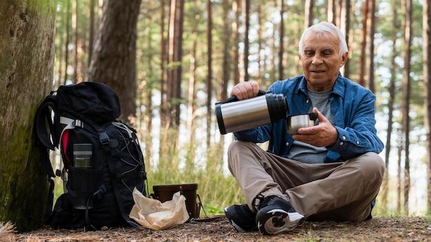 Homme plus âgé voyageant à l'extérieur avec sac à dos