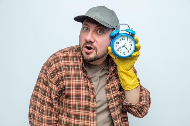 Homme plus propre surpris avec des gants en caoutchouc tenant un réveil
