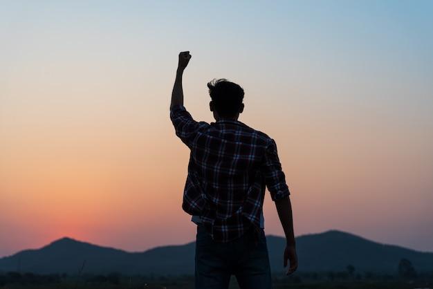 Homme avec le poing en l'air pendant le coucher du soleil, concept de liberté et de courage.
