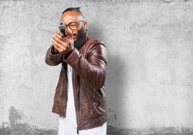 L'homme pointant avec une arme à feu
