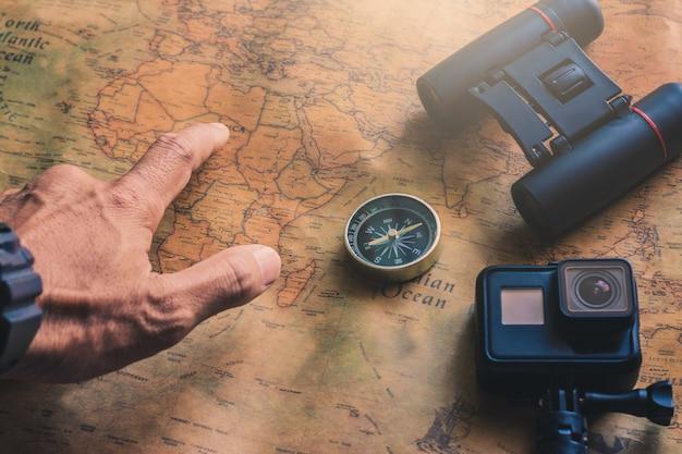 Homme pointant le bloc-notes pour la note avec un crayon de jumelles, une boussole sur une carte en papier pour la découverte de l'aventure de voyage