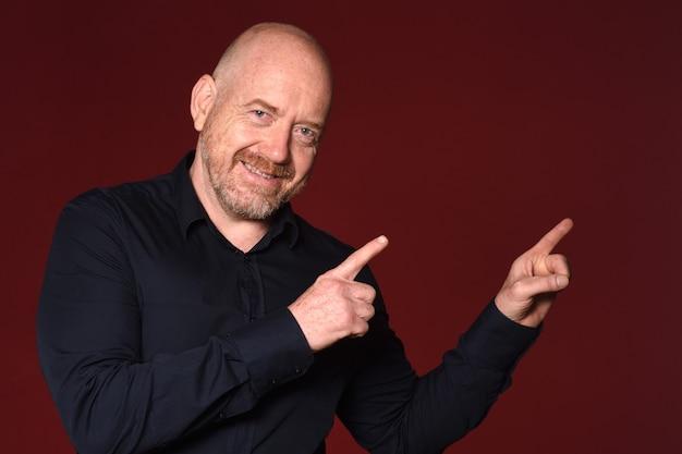 Homme pointant avec deux doigts sur fond rouge