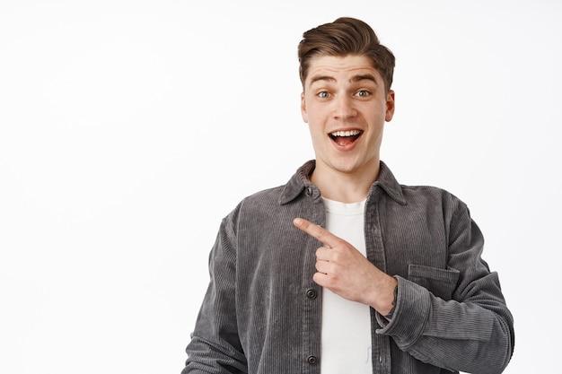 Homme pointant le doigt vers la gauche, souriant excité et l'air amusé, montrant un nouvel événement génial, recommande le produit sur blanc