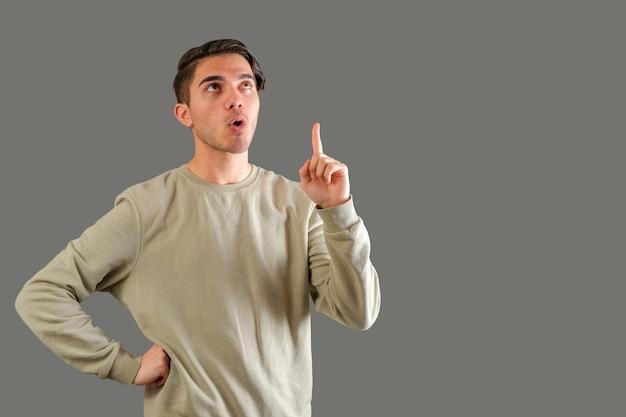 Homme pointant le doigt vers le haut isolé sur fond gris