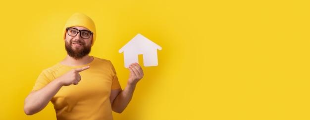 Homme pointant sur la maison sur fond jaune, image panoramique