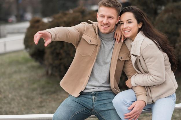 Homme pointant pendant que sa petite amie sourit