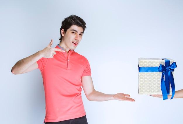 Homme pointant sur sa boîte cadeau blanche avec ruban bleu