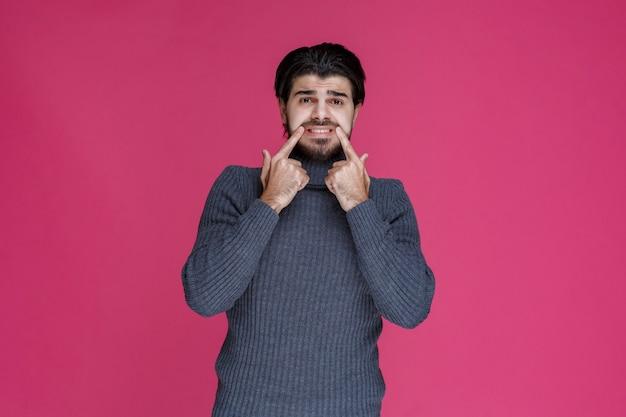 L'homme pointant sa bouche avec les doigts et demande en souriant.