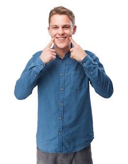L'homme pointant son sourire avec ses doigts