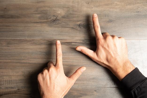 Un homme pointe ses doigts sur une table en bois