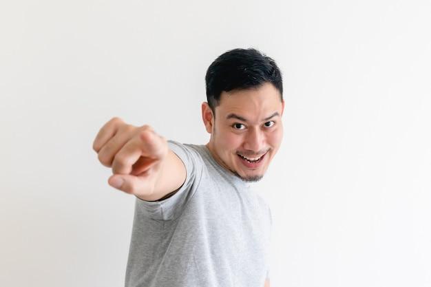 L'homme pointe vers la caméra avec une expression faciale excitée.