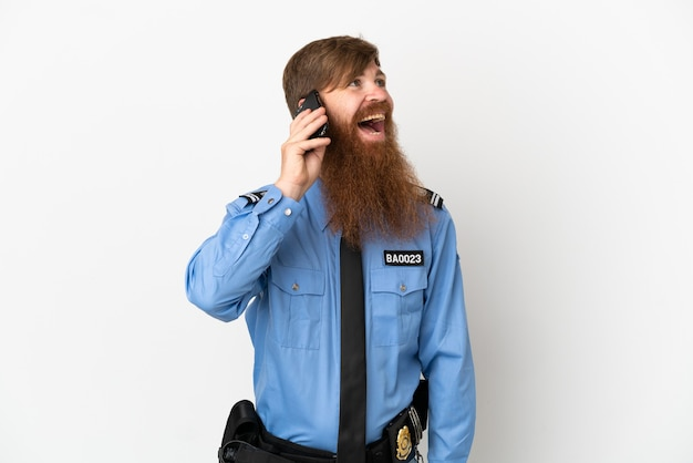 Homme de police rousse isolé sur fond blanc en gardant une conversation avec le téléphone mobile