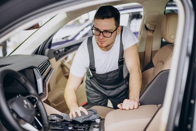 Homme polissant la voiture à l'intérieur au service de voiture