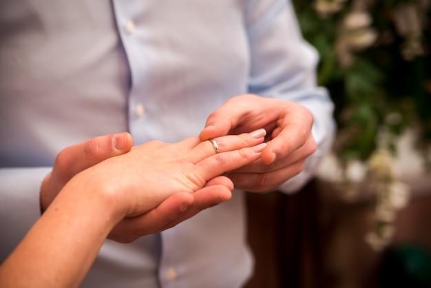 Homme portant une bague de mariage sur la main de la femme