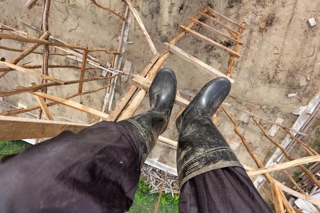 Homme portant une botte à l'aide d'un escalier en bois temporaire en chantier pour monter et descendre.