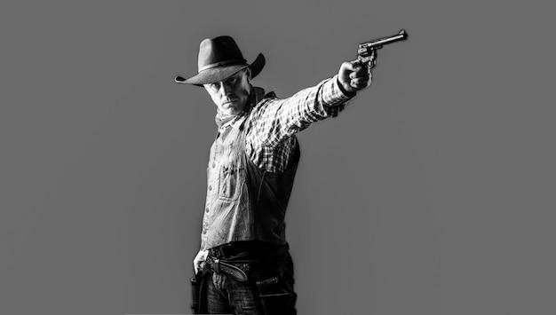 Homme portant un chapeau de cowboy, arme à feu. ouest, armes à feu. portrait d'un cow-boy. owboy avec arme sur fond rouge. bandit américain en masque, homme occidental avec chapeau. portrait d'agriculteur ou de cow-boy au chapeau. noir et blanc.