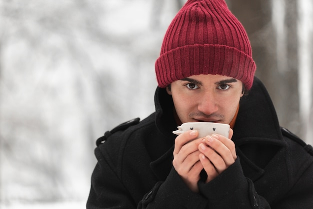 Homme portant un chapeau rouge tenant une tasse de thé