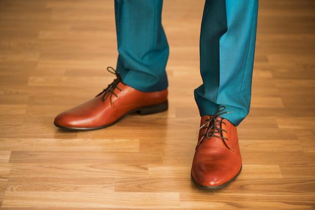 Homme portant des chaussures sur un plancher en bois. concept de vêtements, le marié se prépare avant la cérémonie. détail du corps de l'homme d'affaires.