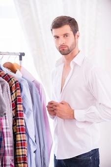 Homme portant une chemise blanche. jeune homme confiant s'habiller chemise blanche et regardant la caméra